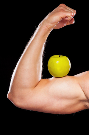 only the biceps: Healthy lifestyle. Cropped image of muscular man showing his perfect biceps with a green apple on it while isolated on grey background