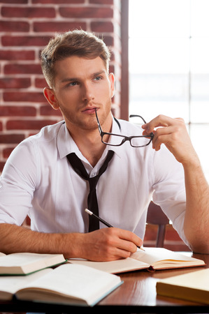 creative writing: Young and creative. Thoughtful young man in shirt and tie writing something in note pad and looking away while sitting at his working place Stock Photo