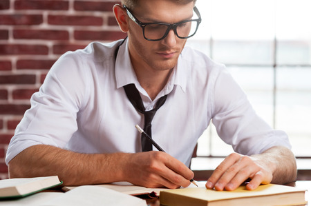 creative writing: Confident and creative. Handsome young man in shirt and tie writing something in note pad while sitting at his working place