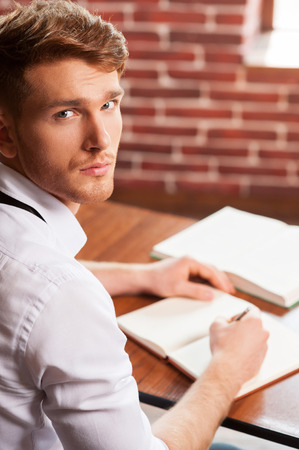 looking over shoulder: Writing his new roman. Top view of handsome young man in shirt and tie writing something in note pad and looking at camera while sitting at his working place