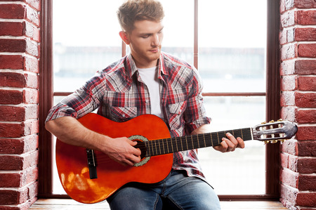 He got creative soul. Handsome young man playing acoustic guitar while sitting on the window sill