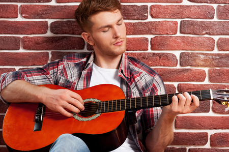 Playing guitar. Handsome young man playing acoustic guitar while leaning at the brick wall photo