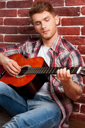 virtuoso: Young and creative virtuoso. Handsome young man playing acoustic guitar while leaning at the brick wall