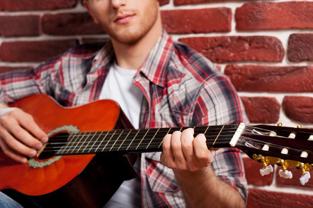 Young virtuoso. Close-up of handsome young man playing acoustic guitar while leaning at the brick wall photo