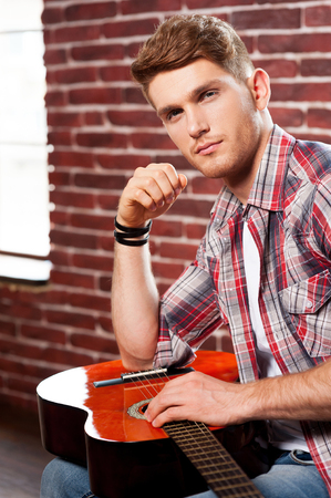 Young and creative. Side view of handsome young man holding acoustic guitar and looking at camera while sitting against brick wall photo