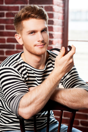 Handsome smoking pipe. Cheerful young man in striped shirt holding pipe and looking at camera while sitting on the chair  photo