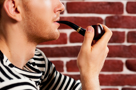Smoking a pipe. Close-up of young man in striped clothing smoking pipe while sitting on the chair  photo