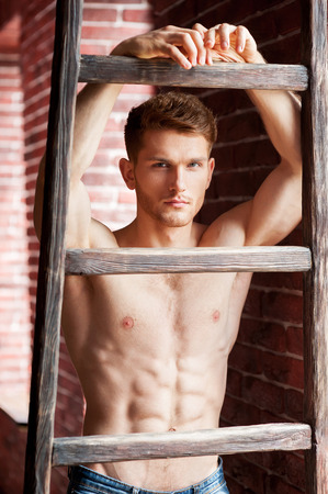 abdominal wall: Flirty handsome. Handsome young shirtless man leaning at the wooden ladder and looking at camera while standing near the brick wall