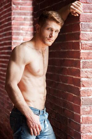 hombres sin camisa: Sentirse coqueta. Hombre sin camisa joven hermoso que se inclina en la pared de ladrillo y mirando a la cámara