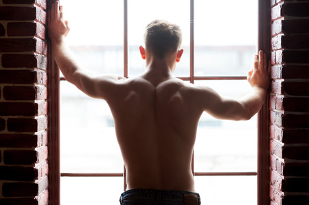 looking through window: Shirtless handsome. Rear view of young shirtless man looking through the window