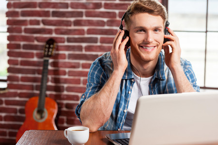 Enjoying music. Handsome young man in headphones working on laptop and smiling while acoustic guitar laying in the background  photo