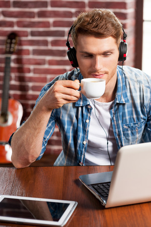 Music is my life. Top view of handsome young man in headphones working on laptop and drinking coffee while acoustic guitar laying in the background  photo
