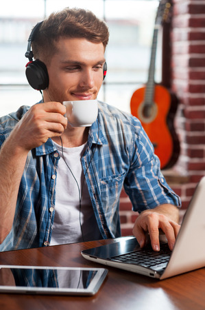 Relaxing with his favorite music. Handsome young man in headphones working on laptop and drinking coffee while acoustic guitar laying in the background  photo