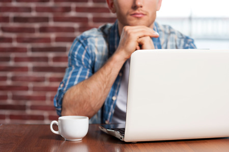 finding out: Finding out solution. Close-up of young man sitting at the table with laptop on it