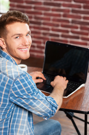 over the shoulder view: Surfing the net is fun. Top view of handsome young man working on laptop and looking over shoulder while sitting at his working place