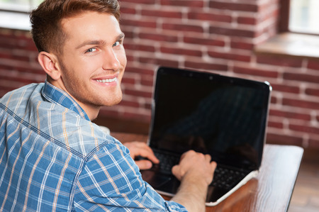 over the shoulder view: Young and creative. Rear view of handsome young man working on laptop and looking over shoulder while sitting at his working place  Stock Photo