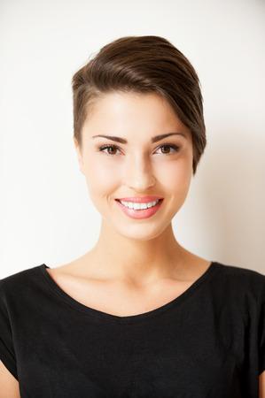 スタイリッシュな美しさ。カメラに笑顔美しい若い短い髪の女性の肖像画 写真素材