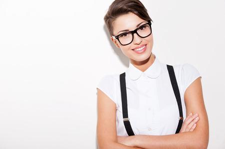 hair short: Fiducioso e di tendenza. Bella giovane donna capelli corti in camicia bianca e bretelle mantenendo le braccia incrociate e sorridente Archivio Fotografico
