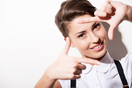 hair short: Messa a fuoco a voi. Bella giovane donna capelli corti in camicia bianca e bretelle messa a fuoco con telaio dito