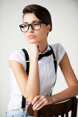 In her own style. Thoughtful young short hair woman in white shirt and suspenders sitting on the chair and holding hand on chin Stock Photo