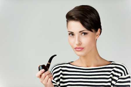 Beauty smoking pipe. Attractive young short hair woman in striped clothing holding pipe and looking at camera photo