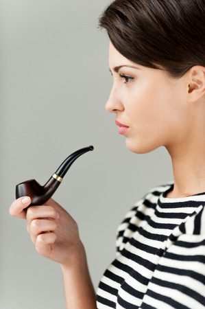 Smoking pipe. Side view of attractive young short hair woman in striped clothing holding pipe and looking away photo