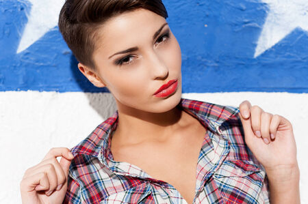 Feeling flirty. Fashionable young short hair woman posing against American flag  Stock Photo