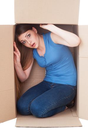 안에 갇혀. 골판지 상자에 앉아있는 동안 카메라를보고 충격을 젊은 여자