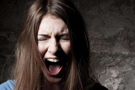 mouth closed: Terrified woman. Terrified young woman keeping eyes closed and shouting while standing against dark background