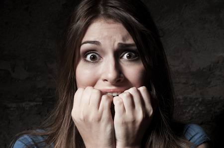 I am so scared! Shocked young woman staring at camera while holding fingers in mouth while standing against dark background