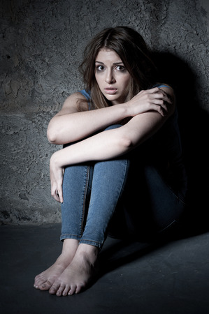 beaten woman: Shocked and terrified  Shocked young woman looking at camera while sitting on the floor in a dark room Stock Photo