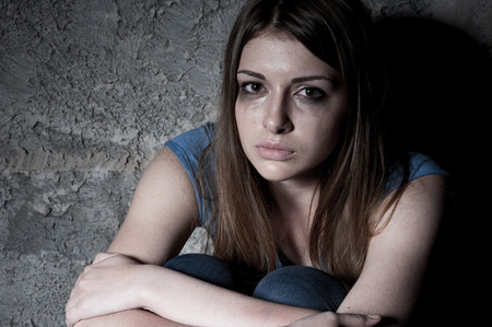 Hopelessness  Top view of young woman crying and looking at camera while sitting against dark wall photo