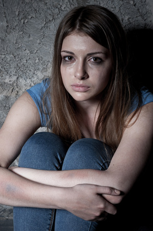 Hopeless woman  Top view of young woman crying and looking at camera while sitting against dark wall photo