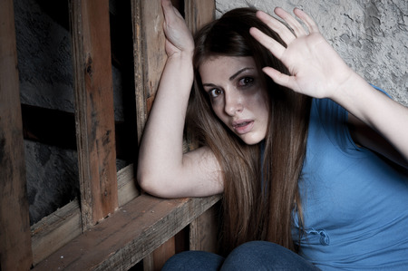 beaten up: Shocked and terrified  Terrified young woman looking at camera and stretching out hand while leaning at the dark wall Stock Photo