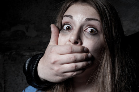 beaten woman: Kidnapping  Terrified young woman with hand covering her mouth staring at camera Stock Photo