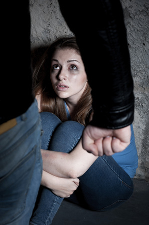 Home violence  Young woman crying and looking at the man standing in front of her and holding fist  Stock Photo