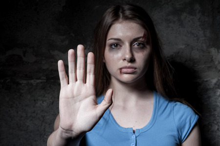 violencia intrafamiliar: Dejar de sufrir la mujer joven golpeado mujer mirando la c�mara y se extiende hacia fuera la mano mientras est� de pie contra la pared oscura