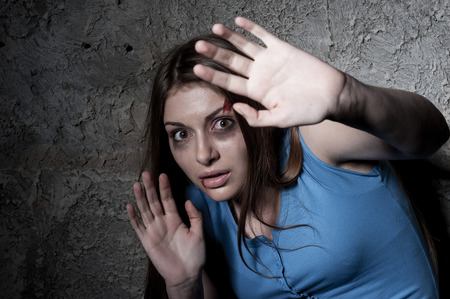 domestic: Please no  Terrified young woman looking at camera and stretching out hand while leaning at the dark wall Stock Photo