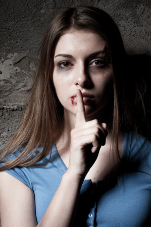 violencia intrafamiliar: No calles joven mujer golpeada que mira la c�mara y la celebraci�n de un dedo en la boca mientras est� de pie contra la pared oscura