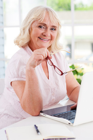 Feeling young and energetic. Happy senior woman using laptop and smiling at camera while sitting at the table photo