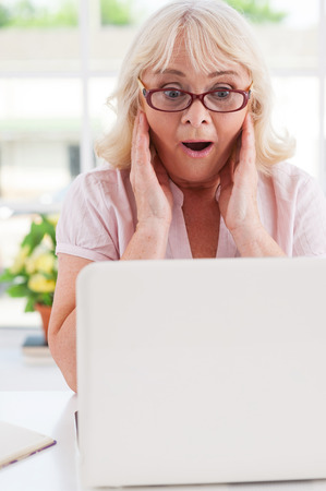 Excited senior woman. Surprised senior woman holding head in hands and expressing positivity while looking at laptop  photo