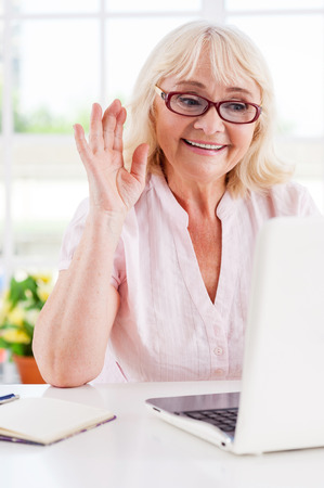 Saying hi to her nearest. Cheerful senior woman waving with her hand while looking at laptop  photo