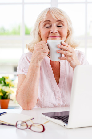 Taking a moment to relax. Cheerful senior woman holding cup and keeping eyes closed while sitting at her working place  photo