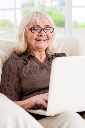 net surfing: Navigare in rete � divertente. Donna maggiore che lavora sul computer portatile e sorridente mentre seduto alla sedia