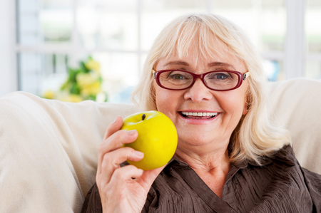 Enjoying healthy eating. Senior woman holding apple and smiling while sitting at the chair photo