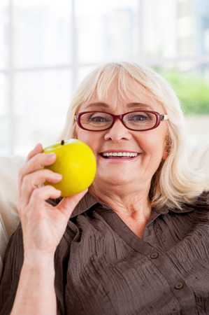 Enjoying healthy lifestyle. Cheerful senior woman holding apple and looking at camera while sitting at the chair photo
