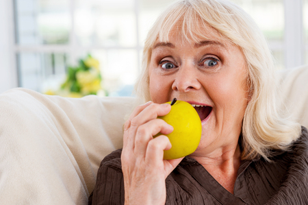 I love apples! Cheerful senior woman holding apple and looking at camera while sitting at the chair photo