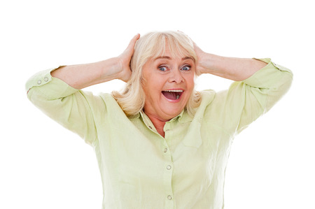 unbelievable: �Incre�ble! Feliz mujer mayor sosteniendo la cabeza en las manos y sonriendo mientras est� de pie aislado en fondo blanco