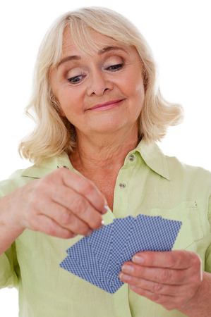one senior woman only: Senior lady playing cards. Cheerful senior woman holding playing cards and smiling while standing isolated on white background Stock Photo
