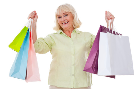 I love shopping! Happy senior woman stretching out hands with shopping bags and smiling while standing isolated on white background